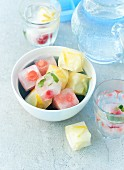 Summer fruit ice cubes in glasses and a bowl