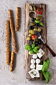 Mediterranean appetizer antipasti board with green black olives, feta cheese, mozzarella, capers, pepper, basil with grissini bread sticks