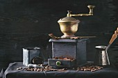 Old vintage grinder with roasted coffee beans and grind coffee in tin jar with scoop over black table with black wooden background