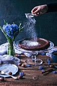 Woman sprinkling powdered sugar on top of Swedish chocolate cake on a cake stand