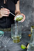 A women is preparing a matcha wine cocktail