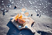Two glasses of white wine and cantaloupe melon slices on a sandy beach