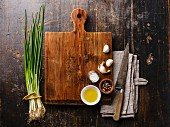 Wooden cutting board background with seasoning, herbs and kitchen knife on wooden background