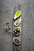 Green food: olive oil, macha tea, olives, pumpkin seed on grey background