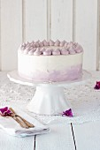 A cream cake with lilac piping