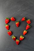 Strawberries arranged in a heart shape on a blackboard