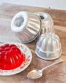Various jelly moulds and red jelly on rustic wooden table