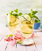 Grapefruit drinks with cucumber spirals and mint sprigs