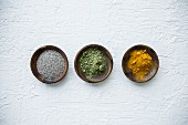 Superfood in small bowls (chia seeds, matcha powder and turmeric powder)