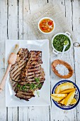Churrasco steak with side dishes (Criolla sauce, chimichurri sauce and potato wedges)