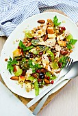 A chicken and corn salad with fruit and almonds