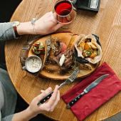 Frau isst Steak mit Ofenkartoffeln und Pilzsauce