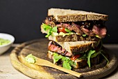 A steak sandwich with wild garlic mayonnaise, balsamic onions, tomatoes and rocket