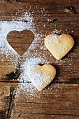Two heart-shaped shortbreads sprinkled with icing sugar on wood