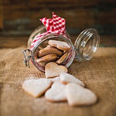 Preserving jar of heart-shaped shortbreads sprinkled with icing sugar on jute