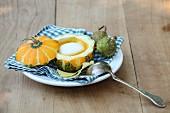 Pumpkin soup with cream served in a mini pumpkin