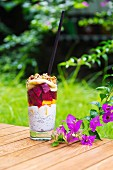Glass of chia pudding with different fruits and cereals