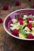 Bowl of avocado raspberry salad with feta, close-up