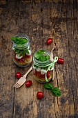 Calabrese salad with pasta, tomatoes, mozzarella, rocket and basil in glasses