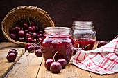 Glasses of homemade cherry groats, dish towel and cherries on wood