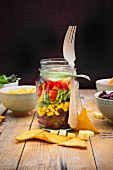 Glass of Tex-Mex salad and ingredients on wood
