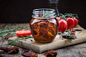 Glass of pickled dried tomatoes with rosemary, close-up