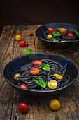 Two bowls of Spaghetti al Nero di Seppia with tomatoes and basil leaves