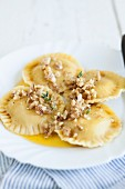 Pumpkin ravioli with melted butter and chopped walnuts