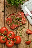 Slice of grain bread garnished with tomato and parsley