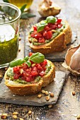 Bruschetta with basil pesto, tomatoes, pine nuts and basil leaves