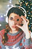 Frau mit Kopfhörer schaut durch ein Weihnachtsplätzchen
