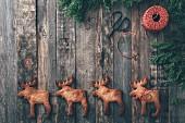 Row of four Elk-shaped Christmas cookies on dark wood