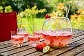 Bowle mit Wassermelone, Erdbeere und Kiwi im Garten