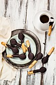 Spoon-shaped biscuits with chocolate icing on plate and a cup of espresso