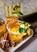 Cocktail mit Weißwein, Zimt, Ananas und Orangenscheiben im Glas mit Zuckerrand