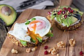 Protein bread slice with cream cheese, sliced avocado and fried egg on wooden board