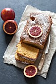 A sliced blood orange cake with icing sugar