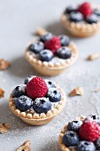 Blueberry and raspberry tarts with icing sugar