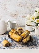Filo rolls with Manouri cheese, walnuts, raisins, and mint; tea, white tulips