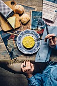 Risotto Milanese on a rustic wooden table with a newspaper, cheese and bread rolls