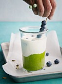 Mango and spinach layered muesli with blueberries