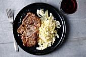Gebratenes Ribeye-Steak mit Rahmsauerkraut
