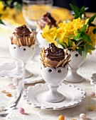 Chocolate eggs in egg cups on a table set for Easter