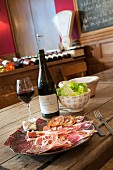 A platter of cold cuts, a side salad and red wine in a wine bar (Mortagne, France)