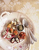 A canapé platter with salmon, walnut, stuffed dates and quail eggs