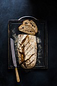 Freshly baked sourdough bread on a chopping board with a knife