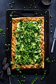 A puff pastry tart with cream cheese, peas, courgette and watercress salad