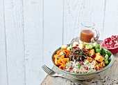 A wild rice bowl with sweet potato, shoots and orange sauce