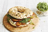 A bagel with crispy tofu, cream cheese and cress