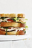 A club sandwich with turkey breast, tomatoes, mozzarella and salsa verde